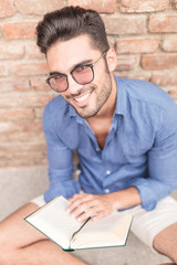 seated casual man with glasses holding a book and smiles