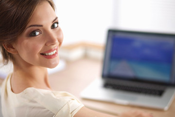 Portrait of beautiful young business woman working on a laptop