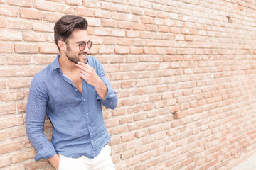 smiling casual man near brick wall wondering about something
