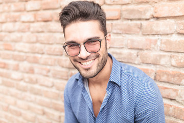 happy smiling  man with glasses leaning against brick wall
