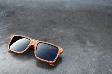 wooden sunglasses and dark glossy background