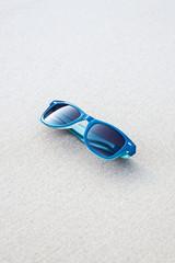 blue plastic sunglasses lying on the sand