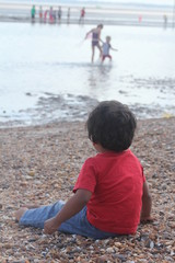young indian toddler boy kid playing sand shore watching sea