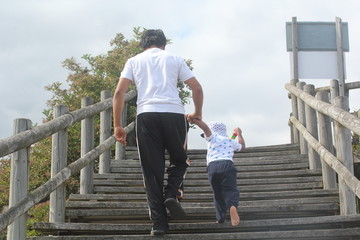 Young father and son holding hands & walking up wooden steps