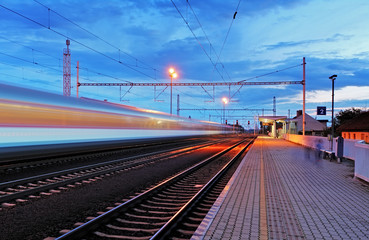 Train station in motion blur at night, railroad
