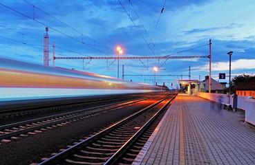Train station in motion blur at night, railroad