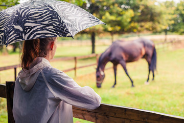 Woman with umbrella looking at horse