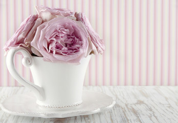 Cup filled with a bouquet of pink roses