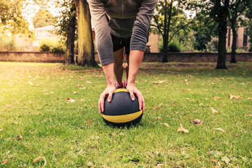 Young woman exercising with medicine ball in park