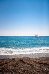 Boat on blue sea and rock beach