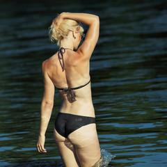 Portrait of young woman in bikini near water. Outdoors.