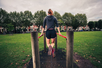 Young woman doing dips in the park