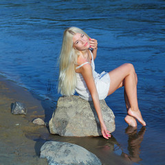 Romantic sweet girl sitting on a rock by the sea