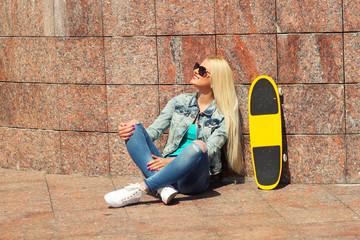trendy girl in jacket sitting on a skateboard