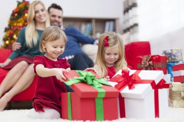 Sweet little girls opening Christmas presents