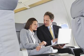 Geschäftsmann und Geschäftsfrau auf Laptop in der Business Class