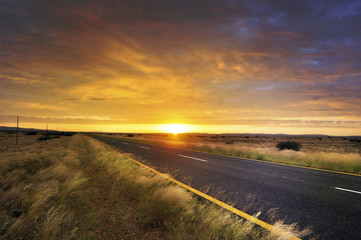 Long road through African country side at sunrise