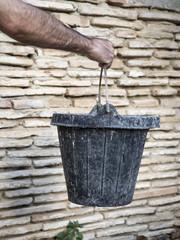 Obrero albañil con un cubo de goma con las manos