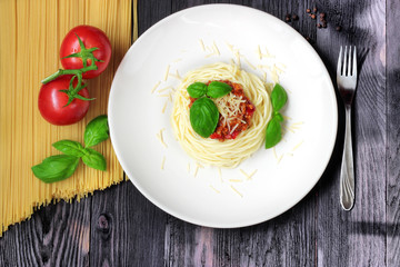 Spaghetti on white plate with pasta and tomatoes