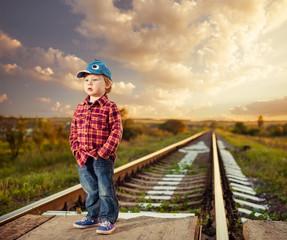 stylish countryside boy at railway sunset