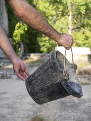 Manos de un hombre vaciando un cubo de goma de albañil