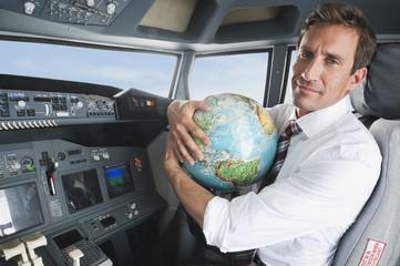 Geschäftsmann mit Weltkugel im Flugzeug-Cockpit
