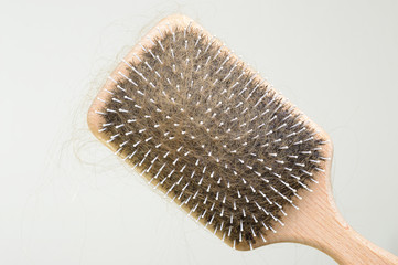 Haarbürste voller Haare wegen Alopezie heller Hintergrund totale
