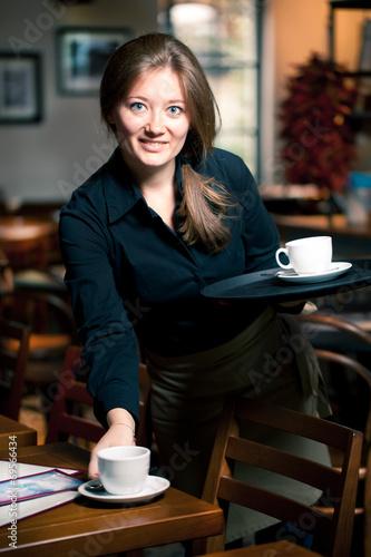 Junge kellnerin arbeitet im Cafe  - 69566434
