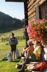 Älteres Paar sitzt vor Almhütte, Bauer trägt Milchkanne