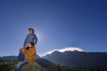 Paar in den Bergen, Mann stehend, Frau sitzt