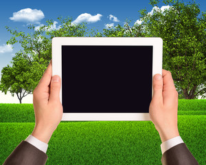 Digital tablet in hands with grass field and trees as backdrop