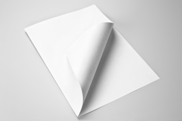 Blank folded sheet of paper with curled corner