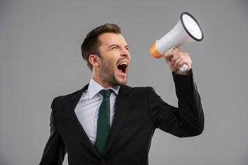 Businessman screaming in megaphone isolated on grey background.