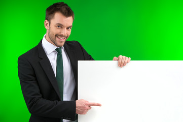 Happy smiling business man showing blank signboard.