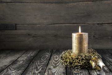 Weihnachtlicher Holz Hintergrund mit goldener Kerze als Karte
