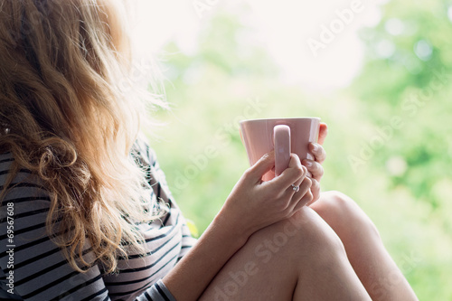 Peaceful woman relaxing at home with cup of tea or coffee poster