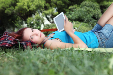 student in park with digital book and headphones
