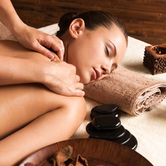 Beautiful woman relaxing with back massage at spa salon.