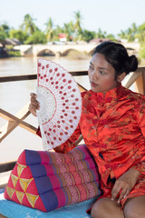 Asian woman resting on the porch
