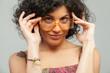 Ragazza mora che regge i suoi occhiali da vista con sguardo sexy