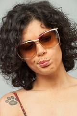 Ragazza indecisa e dubbiosa con degli occhiali da sole