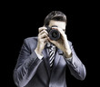Male photographer focusing and composing an image on black