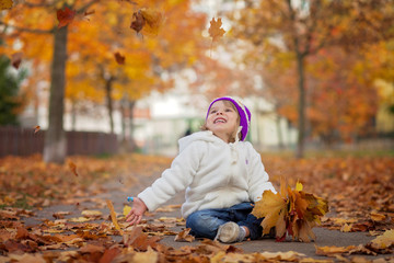 Adorable little girl in the park, playing with leaves