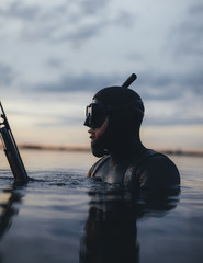 Underwater hunter in sea during evening