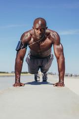 Shirtless young man doing push-ups