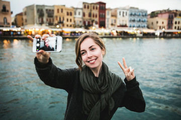 Pretty young female tourist takes travel selfie in Venice, Italy