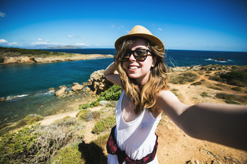Pretty young female tourist takes travel selfie at the beach