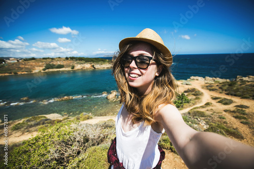 Pretty young female tourist takes travel selfie at the beach - 69573871