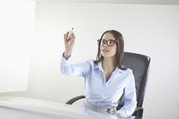 Business-Frau schreibt auf Tafel