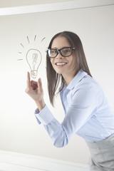 Business-Frau mit gezeichneten Glühbirne auf wischen Bord